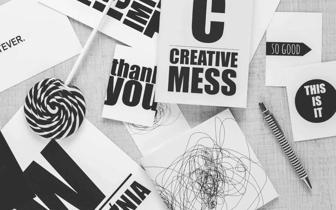 """papers and handbook with """"creative mess"""" written on it"""